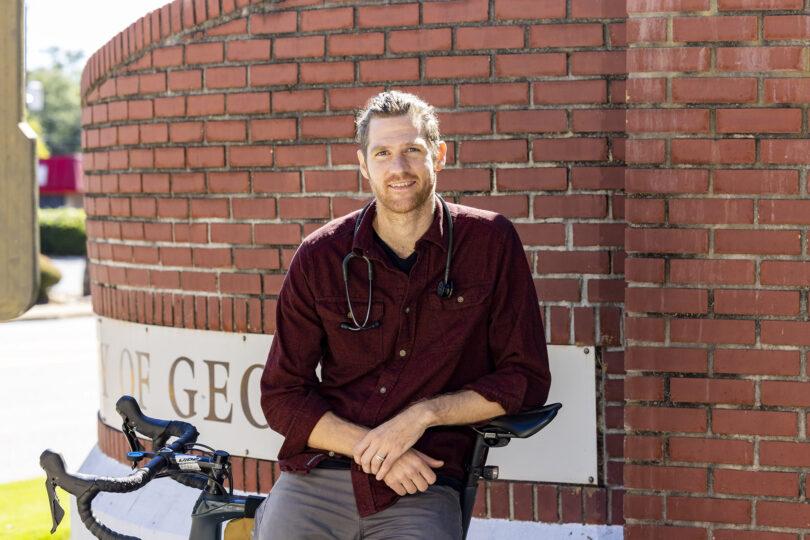 Brett Manger leaning against brick building