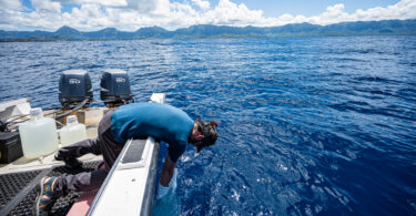 Man leaning over edge of boat to gather water samples.