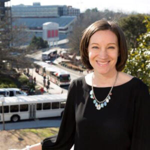 Malissa Clark poses outdoors with buses in the background.