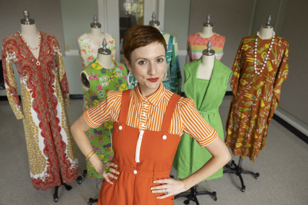 Sara Idacavage poses in front of vintage clothes.