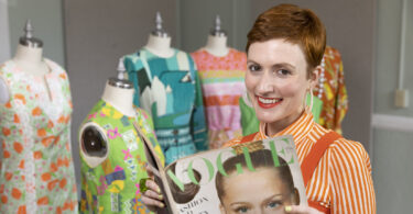 Sara Idacavage holds a vintage magazine in front of vintage clothes.
