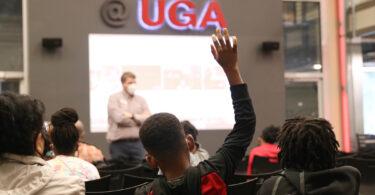 boy facing away raises his hand in auditorium