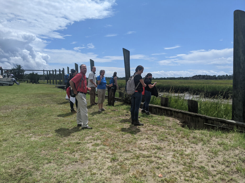 The students stand outside and look at a salt marsh.